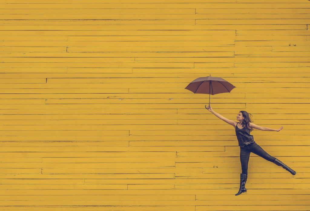 Woman with umbrella in front of yellow background